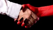 Businessman making a deal with devil, isolated on black background