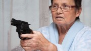 Scared senior woman aiming a gun indoors.