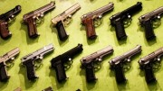 All kinds of different handguns displayed on green background for sale